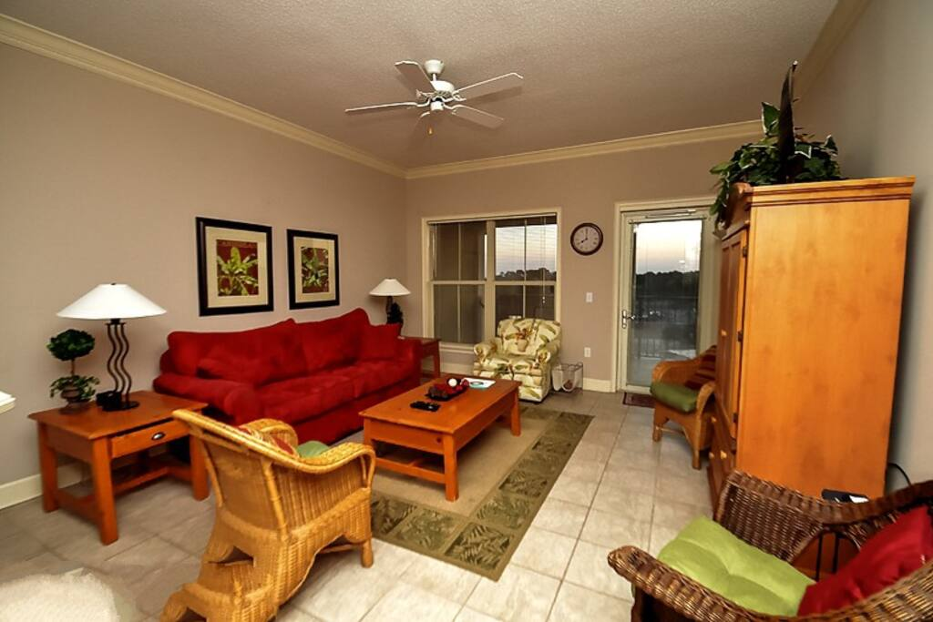 Living room has flat screen TV and access to the balcony with views of the ocean in the distance.