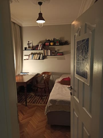 Private room with a single bed, desk and wardrobe