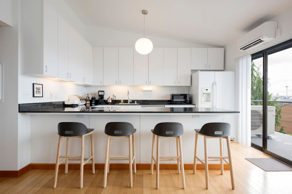Fully stocked kitchen features generous granite U-shaped counter complemented by sustainable Emeco Alfi stools designed by award-winning British designer Jasper Morrison.  Italian Murano lighting by Leucos.