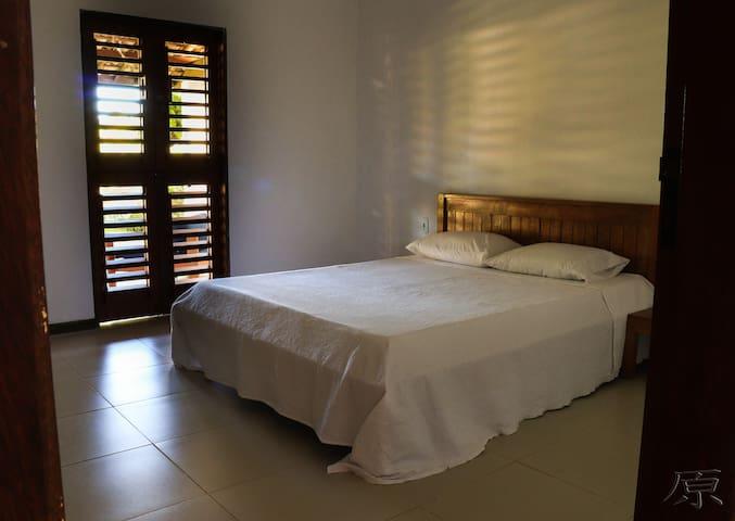 Quarto térreo com cama queen size e ar condicionado