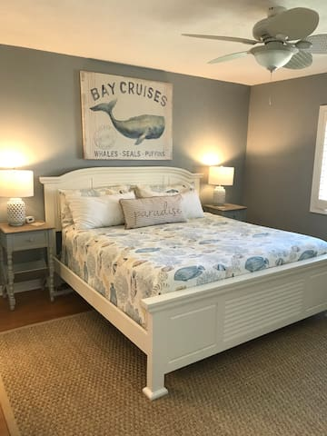 Spacious master bedroom with king size bed, large dresser, and TV.