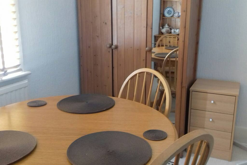 dining table, chairs , wardrobe and chest of draws in bedroom.