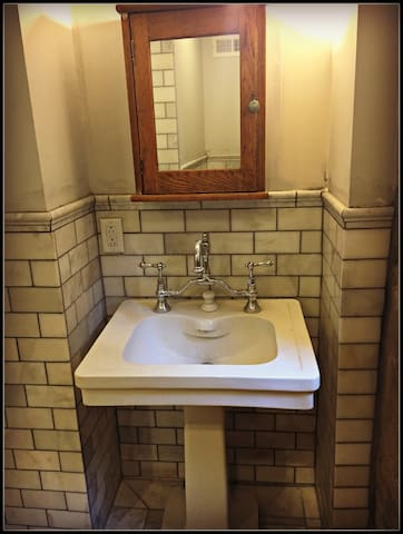 1926 fireclay sink from Savannah GA with marble wainscoting and an antique oak Craftsman medicine cabinet.