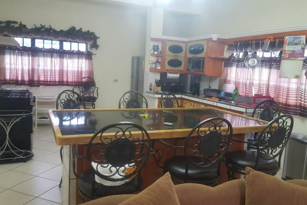 The kitchen is fitted with a large island separating the open floor plan of the unit, where 8 persons could sit and enjoy a great Tobago style meal