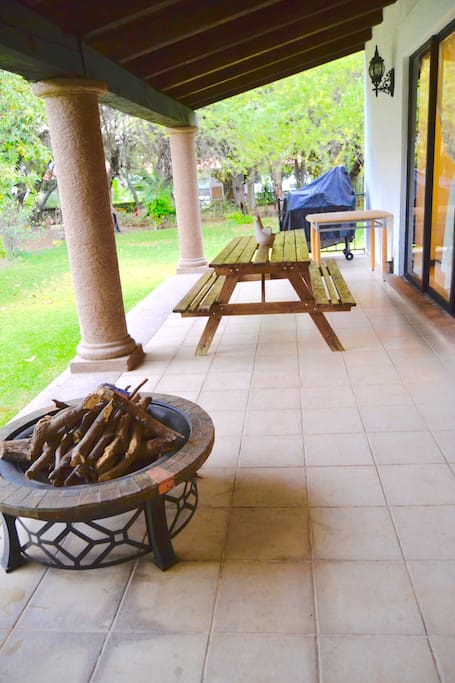 Terraza con asador mesa exterior y chimenea de exterior
