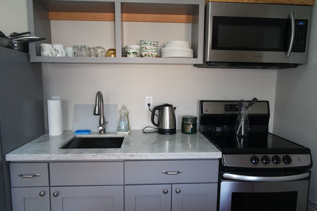 Close up of the studio kitchen complete with stove, oven, microwave, small refrigerator, toaster, coffee maker, and hot water boiler.