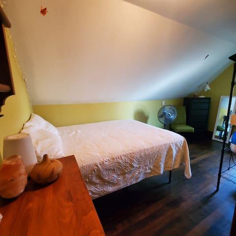 Smaller bedroom with queen, no closet but has dresser and garment rack