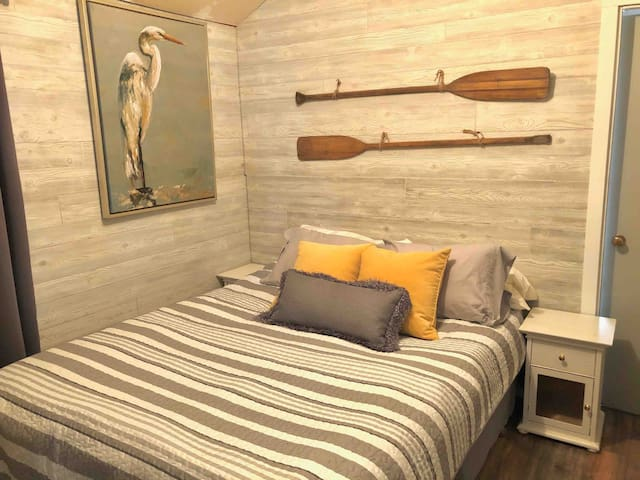 Queen bed with mounted flat screen smart tv and dresser