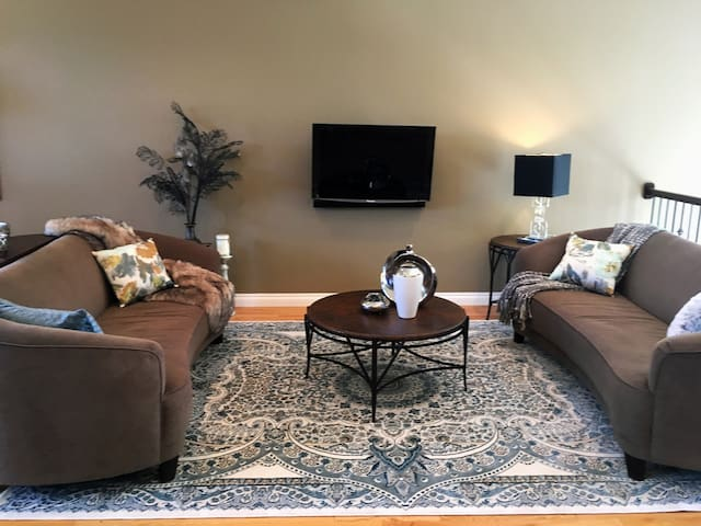Main Living Room with 2 large couches and adjustable wall mounted TV.