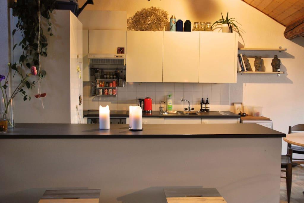 La cuisine, moderne et ouverte sur le salon, et le bar.