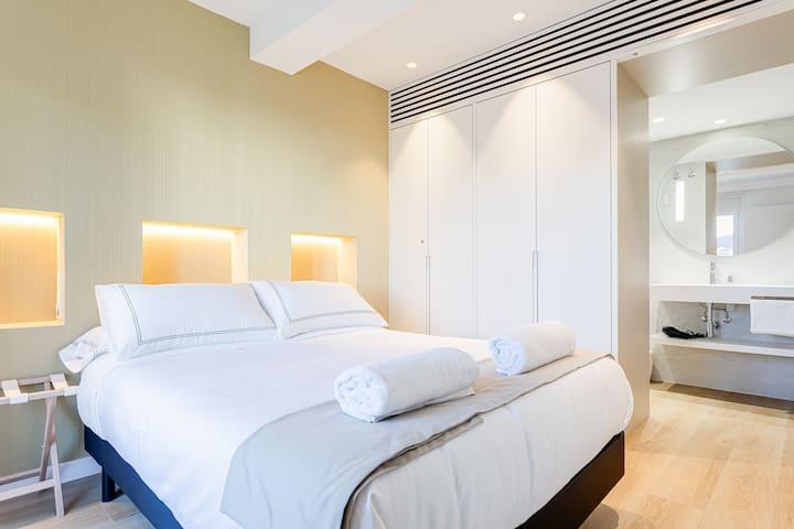 Double bed bedroom facing its own bathroom (open door)