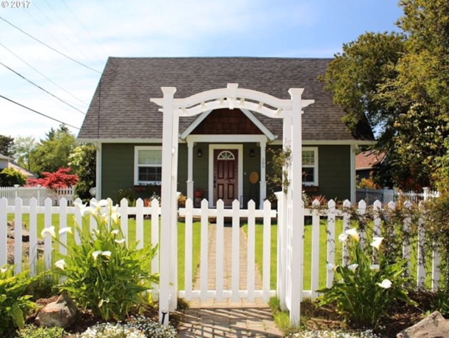 Gated front yard with mature perennial garden.