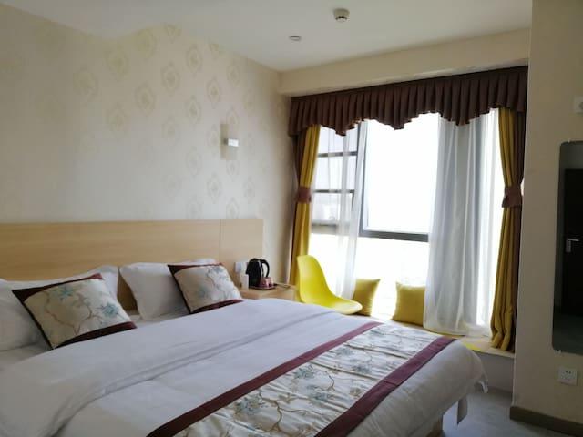 1.8米的双人床,床垫厚25公分,软硬适中。3米多宽的落地大玻璃窗,可以远观华宇天空花园小区美景