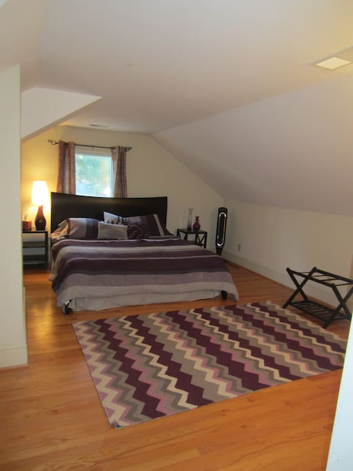 Spacious bedroom has king sized bed, walk-in  closet, dresser, chest of drawers, luggage rack and fan.