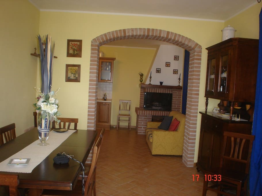 Living piano-terra con tavolo grande ed uno più piccolo, cucina e caminetto funzionante con divano.