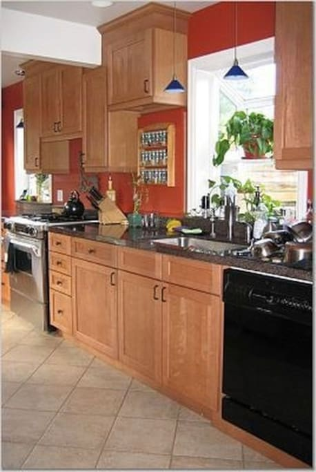 Full kitchen with stainless steel appliances, granite slab counter tops, and gas range.
