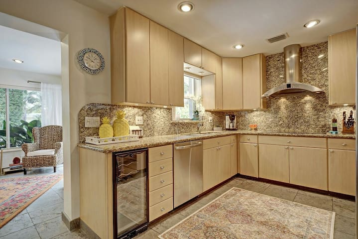 Chef's kitchen with stainless steel appliances, wine chiller, all cooking utensils. Opens to dining room and outdoors