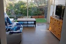 Véranda avec canapé lit 140 et accès extérieur