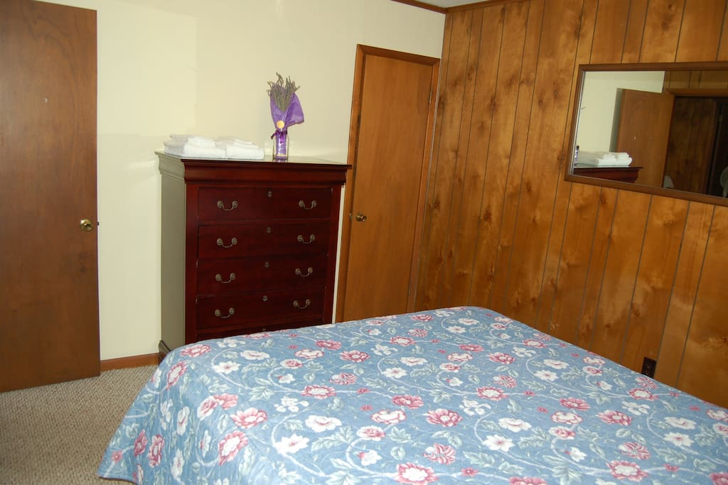 Closet and dresser in room with queen bed.