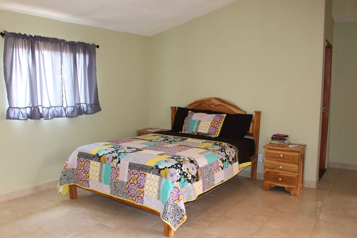 Master bedroom with queen bed and ensuite bathroom.  Sliding glass doors open up to covered back patio.   AC in this room.