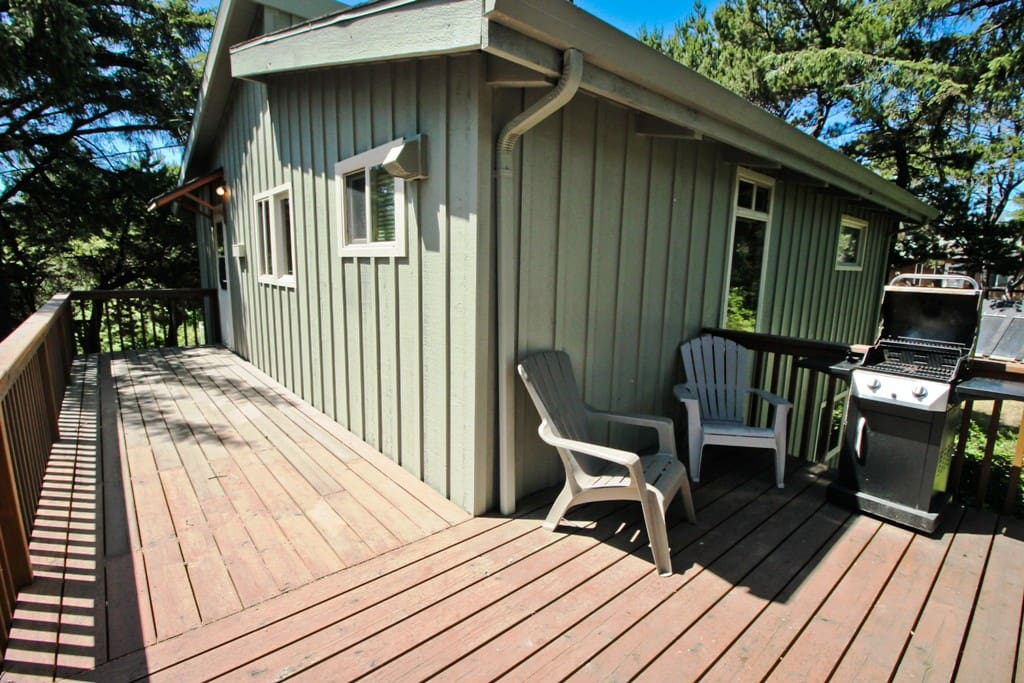 """""""L"""" shaped upper deck with a gas BBQ, patio table and chairs."""