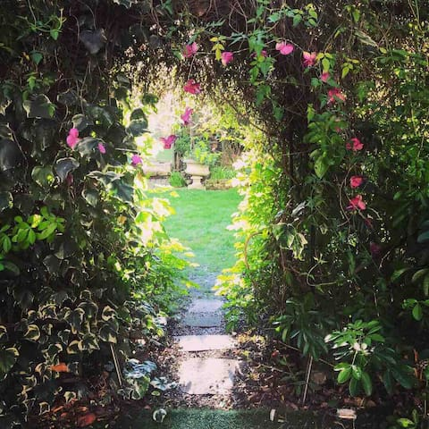 A cute archway leading from the Private garden into the award-winning garden with ponds and fountains