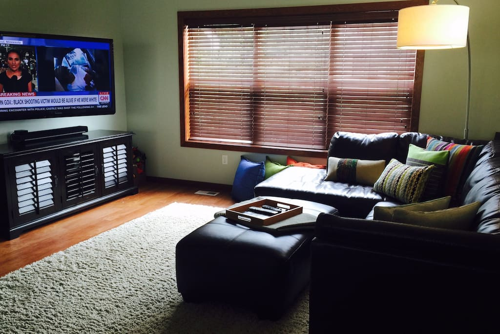 """Relax in the living room with a 55"""" Smart TV and lots of comfy pillows. Log in to your Netflix and chill!"""