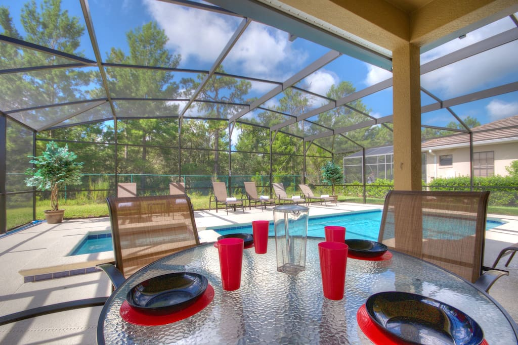 Fully shaded lanai area for al fresco dining by the pool.