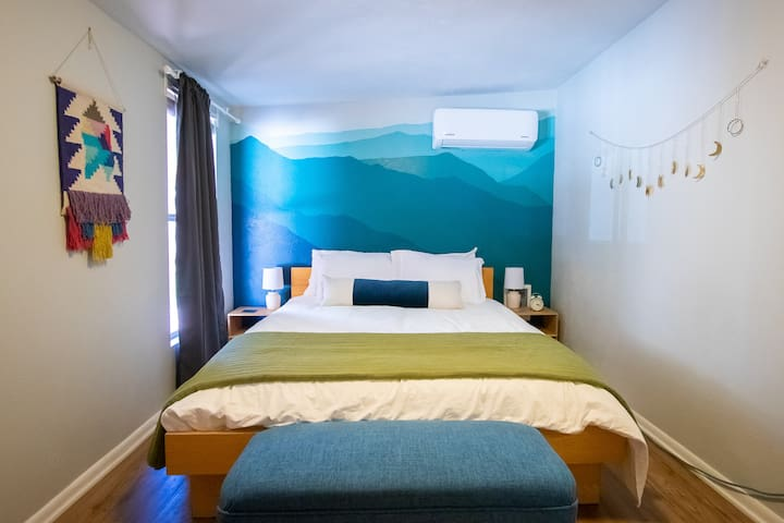 1st bedroom with queen bed. Sleep peacefully with a headboard of mountains, a mural painted by Amelia (Co-Host).