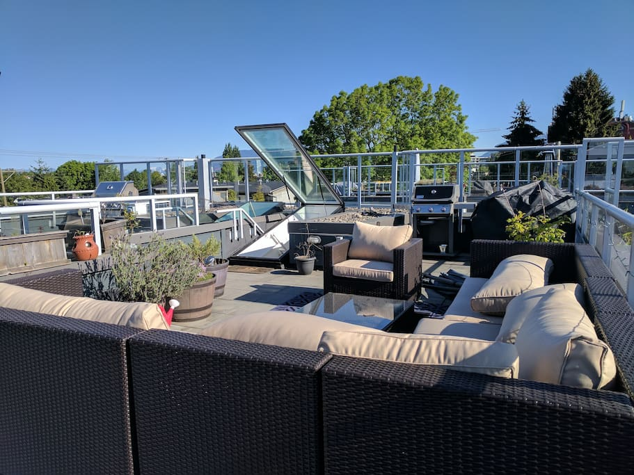 Rooftop patio with large sectional, shade umbrella, heater, BBQ, and bistro table for two
