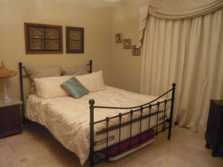 Guest bedroom. Queen-size bed with Sealy posturepedic mattress. Has a trundle bed under to sleep a child if required.