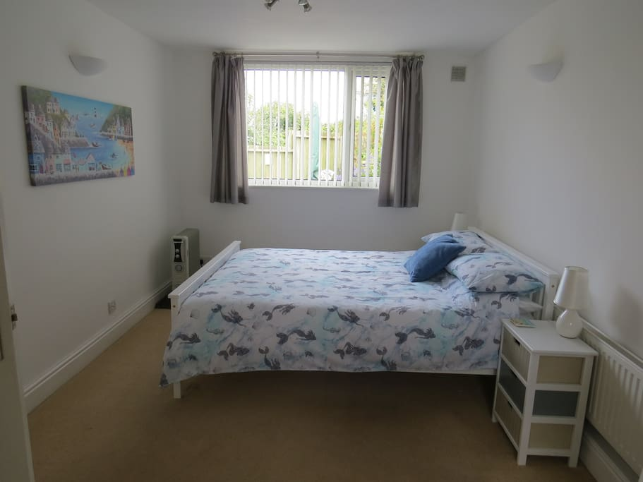 Spacious light bedroom with king size bed
