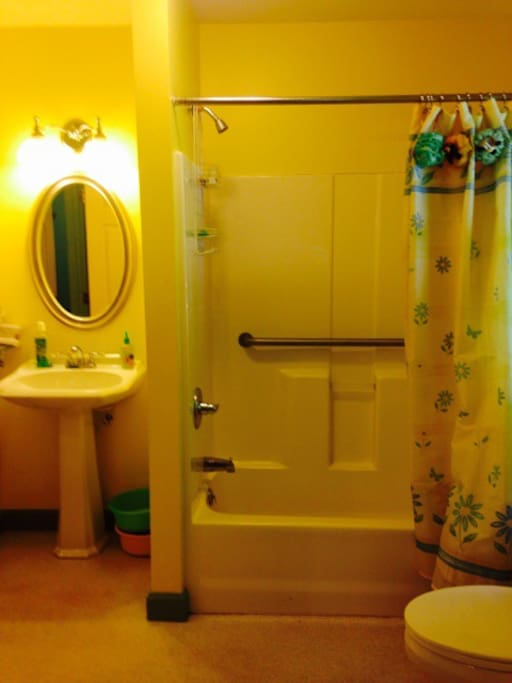 The shared bathroom has a door directly from the Aqua Room into the charming yellow and bright bathroom with a window (with a blind) that looks out into the backyard.  The pedestal sink has a mirror above it and a shelf beside it for personal items.