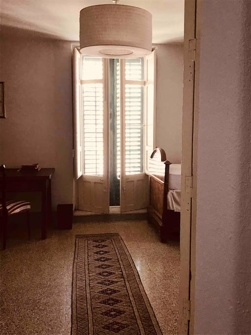 Entry to the bedroom with double doors that open onto a wraparound balcony overlooking the main piazza