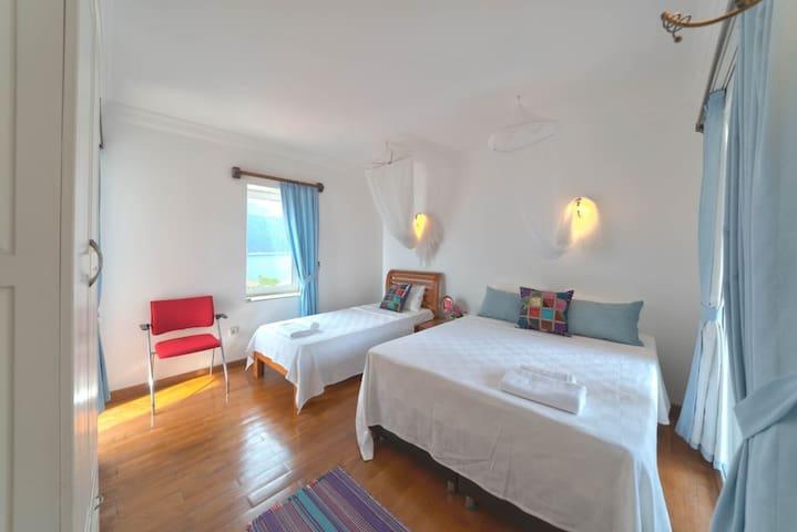 schlafzimmer mit einzel und doppelbetten.