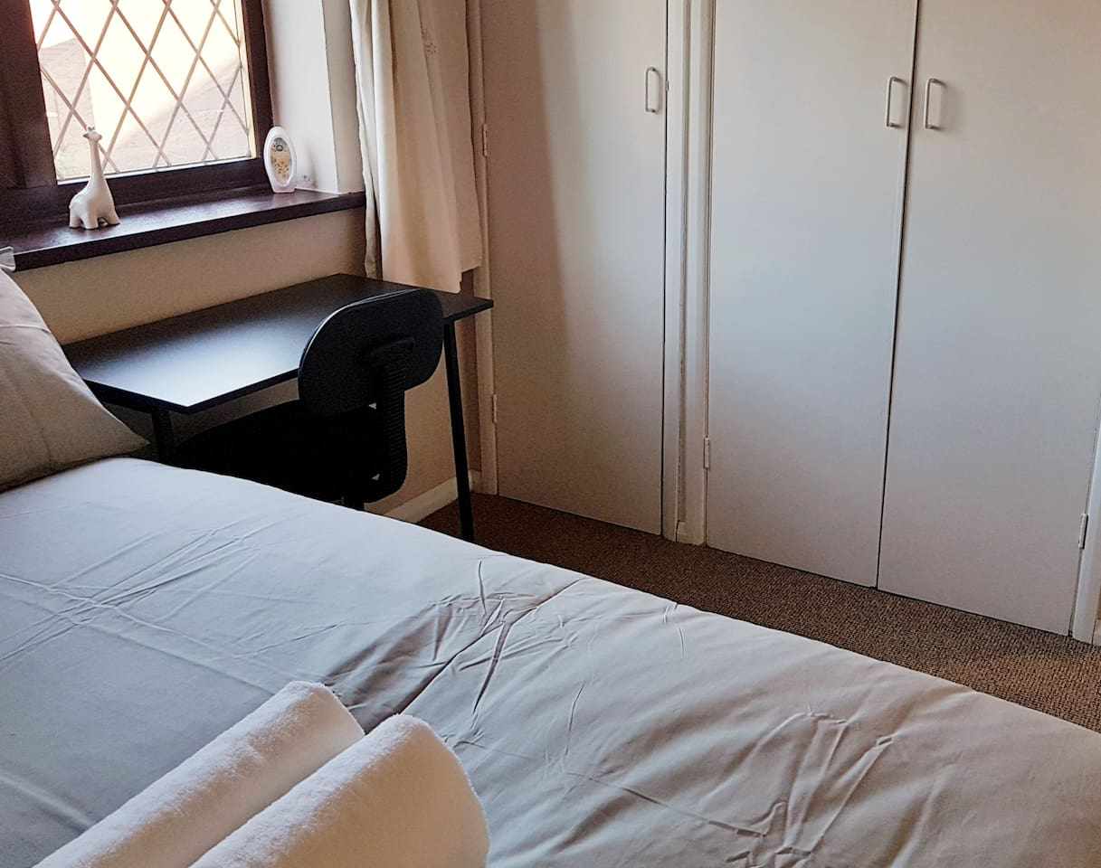 Cozy double room for up to 2 people sharing a small (4ft) double bed. Wardrobe & Storage Space, desk & chair, freshly laundered bed linen and towels, full length mirror.