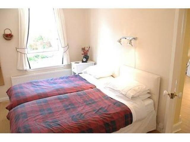 Twin bedroom with en-suite bath and shower