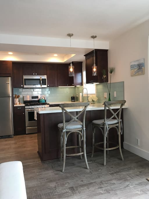 Gleaming new kitchen with new stainless appliance, glass tile backsplash and quartz counters new
