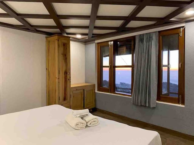 Master bedroom with a panoramic view  of Mussoorie, Dehradun valley and the mountains with winter line.