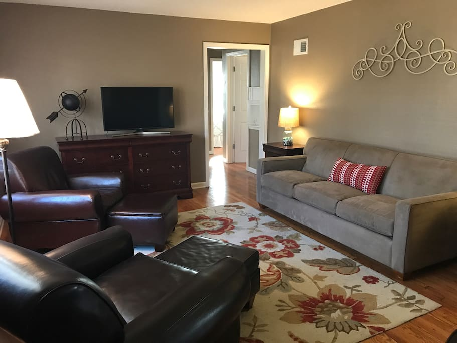 Casual living room.  Comfortable sofa with 2 leather chairs with ottomans.  40 inch television and 100 megabits per second Wifi throughout the house.