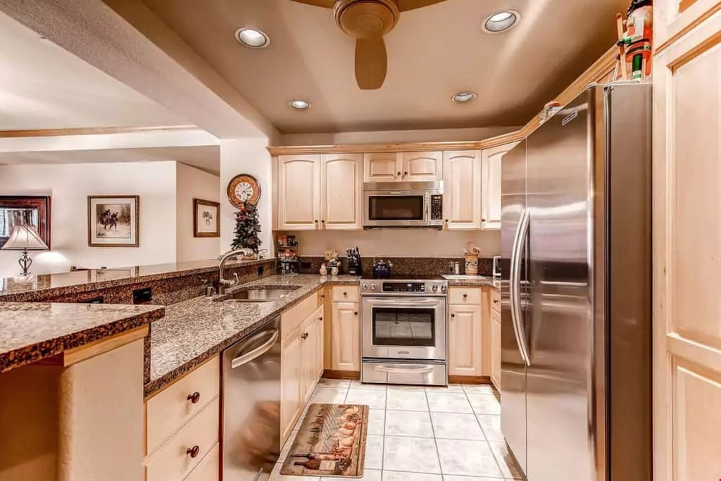Prepare your meals in the fully-equipped kitchen featuring modern stainless steel appliances and granite countertops