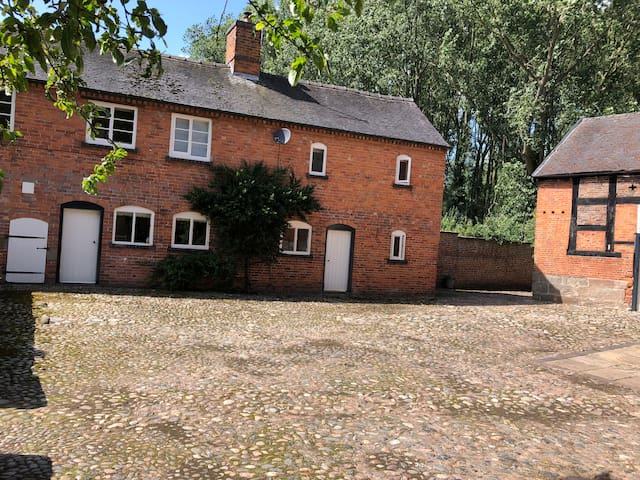 The view of the cottage from the traditional cobbled yard where there is ample parking.