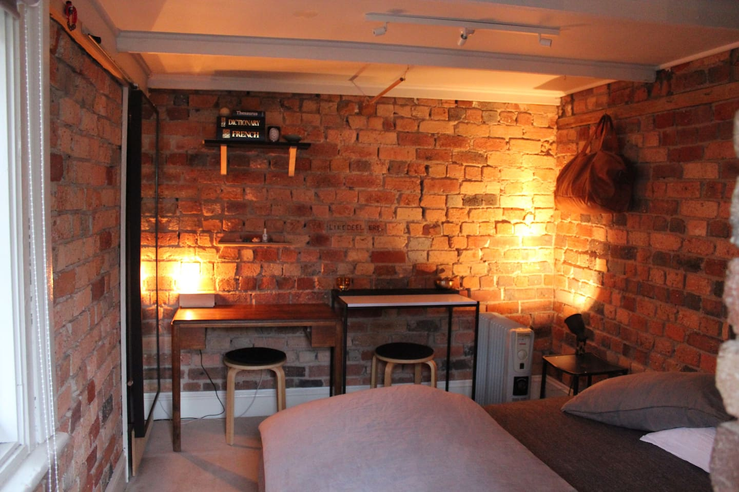 The room has a double bed and a writing desk