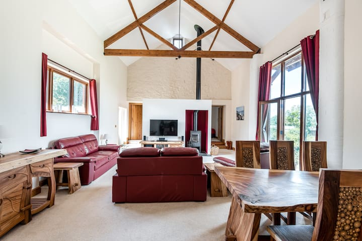 The Barn lounge and dining area, upstairs to take advantage of the views, with log burner and vaulted ceiling.