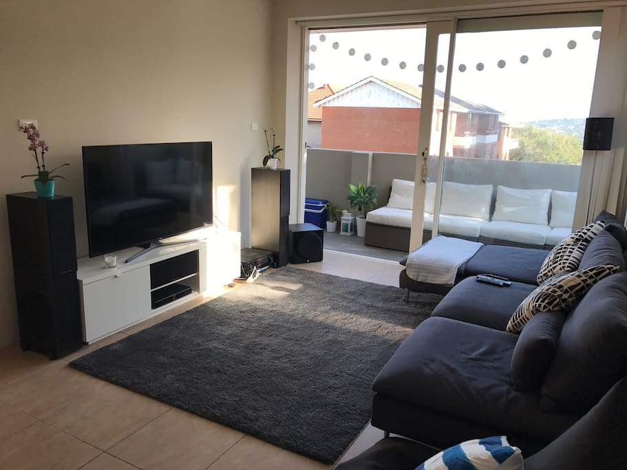 Spacious living area with surround sound system and Foxtel.