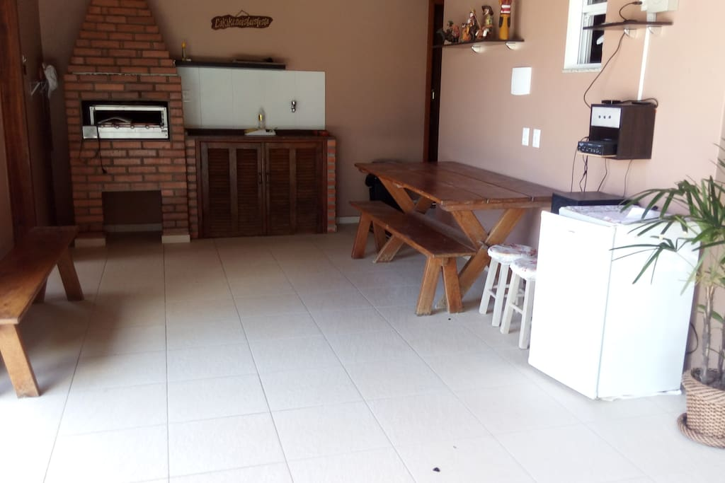 Área Gourmet com churrasqueira, mesa e equipamento de som ambiente