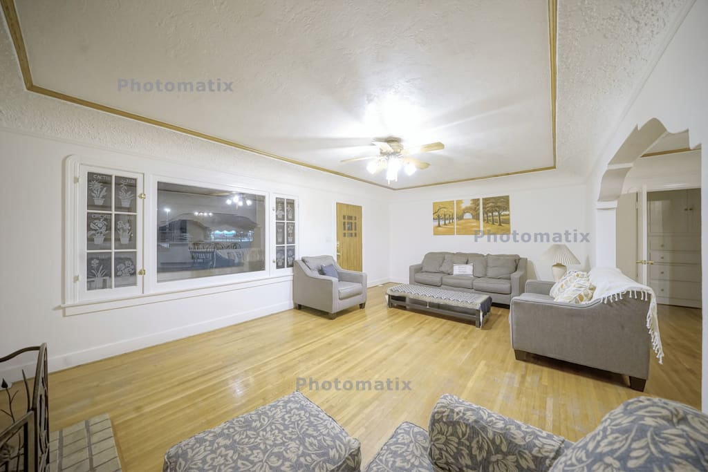 It is a living room with large and beautiful windows. You can see grass and palm trees in the front yard. Of course, curtains are also installed.