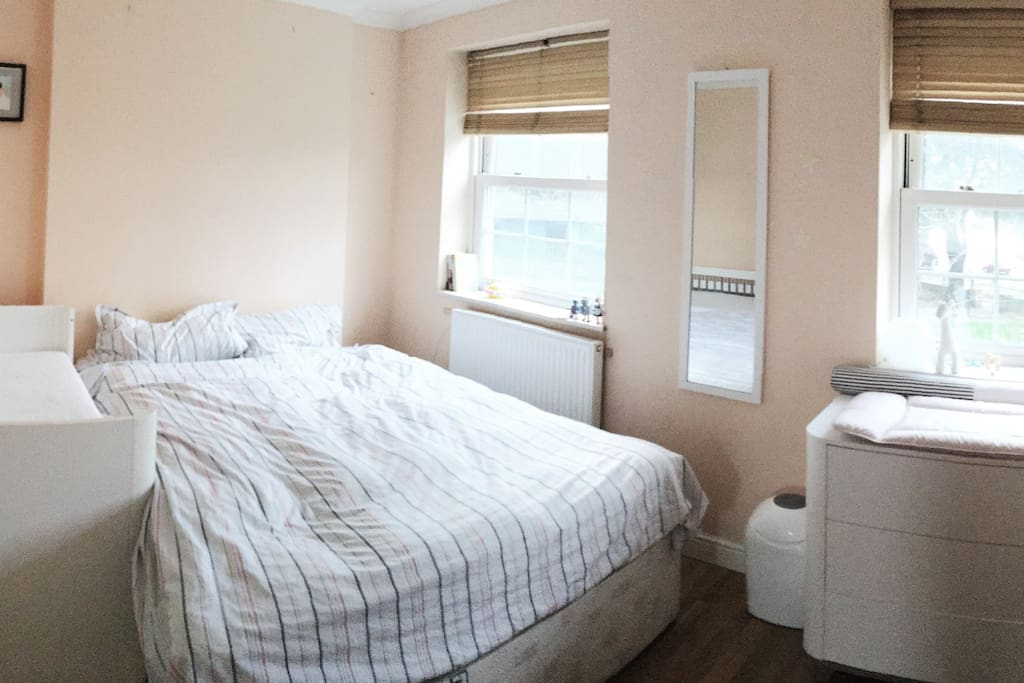 Main bedroom with a double bed and a baby cot