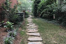 Stepping stone pathway around the side of our house which leads from the parking spot in our driveway to the entrance of our space.
