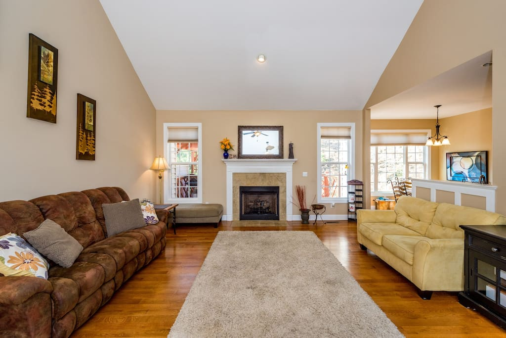 The spacious living room features vaulted ceilings, hardwood floors, and a gas fireplace.